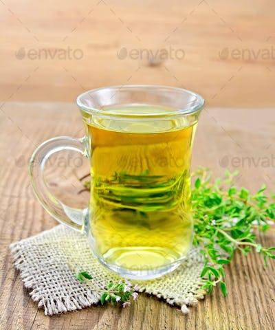 Tea of thyme in mug on wooden board