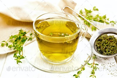 Tea of thyme in cup on light board