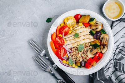 Healthy dinner buddha bowl lunch with chicken, quinoa, grilled and fresh vegetables.