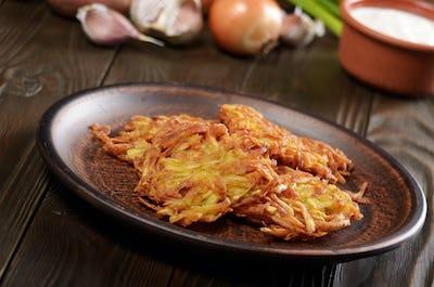 Fresh homemade tasty potato pancakes in clay dish on rustic wood