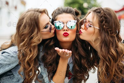 Gorgeous teenagers in sunglasses kissing their friend smiling at camera with heart gesture