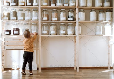 A rear view of small toddler boy standing by shelf with glass jars in zero waste shop.