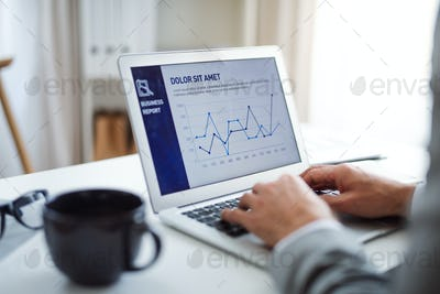 A midsection of businessman with laptop sitting at the table, working.
