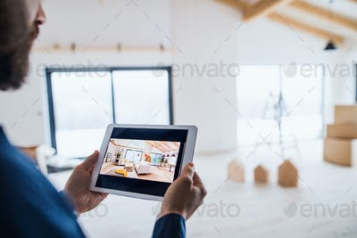 Midsection of man with tablet, looking at interior design sketches. A new home concept.