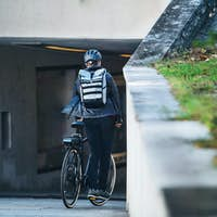 A rear view of male bicycle courier delivering packages in city. Copy space.