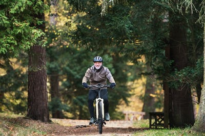 A senior man with electrobike cycling outdoors on a road in park in autumn.