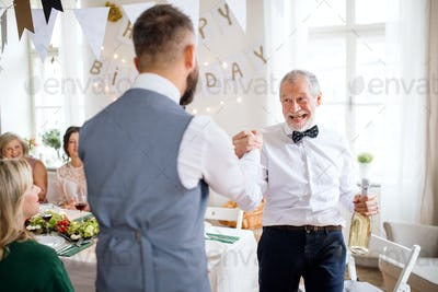 A man giving a bottle of wine to his father on indoor birthday party, a celebration concept.