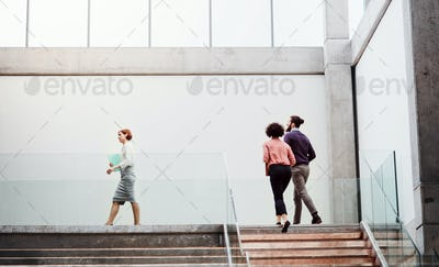 Young businesspeople at work, walking up the stairs.