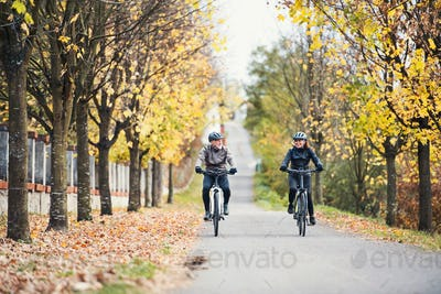 A senior couple with electrobikes cycling outdoors on a road.