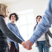 Group of people standing in a circle and holding hands during therapy.