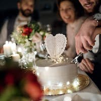 A midsection of young couple sitting at a table on a wedding, cutting a cake.