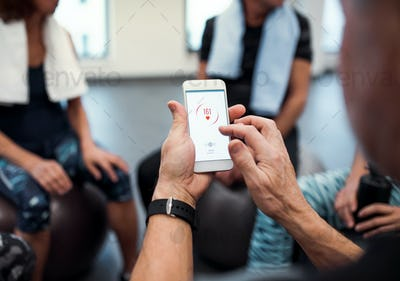 A midsection of group of seniors with smartphone in gym checking heart rate.