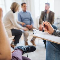 A midsection of counselor with clipboard talking to a client during group therapy.