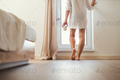 A rear view of young woman with night shirt standing by the window in the morning.