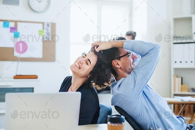 Two young cheerful businesspeople relaxing in a modern office.