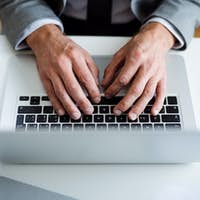 A midsection of businessman with laptop sitting at the desk, working. A top view.