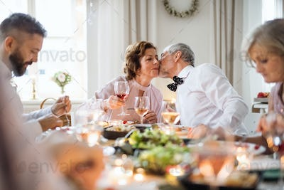 A senior couple sitting at a table on a indoor birthday party, kissing.