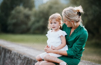 Young mother in nature with small daughter, sitting on a stone wall.