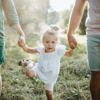 A midsection of young family with a small daughter walking in sunny summer nature.