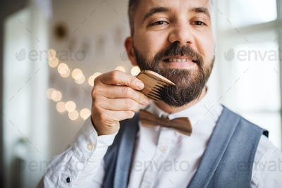 Hipster man standing indoors in a room set for a party, combing beard.