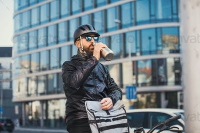Male courier with sunglasses drinking water when delivering packages in city.