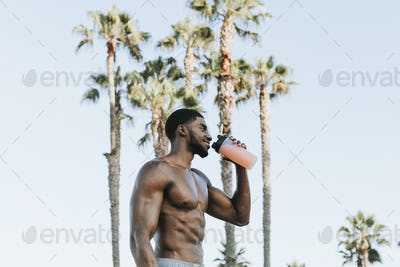 Muscular man drinking a protein shake
