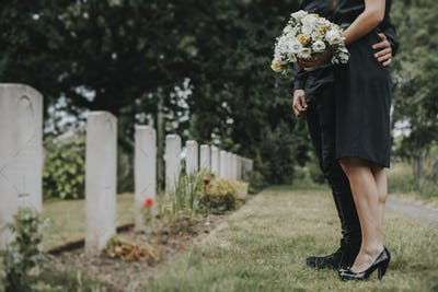 Couple standing together by a gravestone