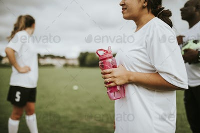 Female football player holding a water bottle