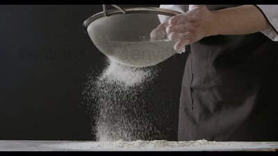 Flour sifter in the hands of a chief female in a black apron on a dark background. Slow motion, Full