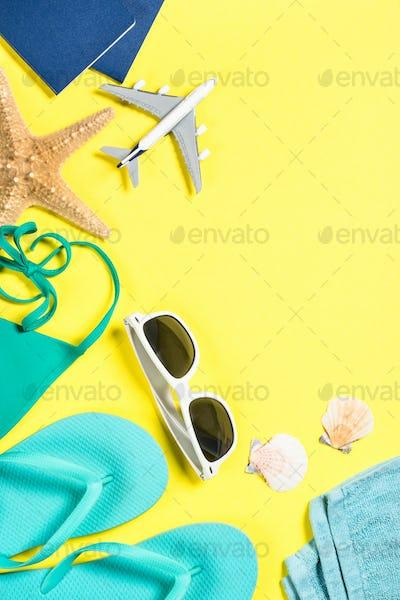 Blue flip flops, sunglasses, passport, plane and starfish on yellow background
