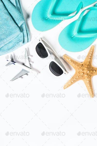 Blue flip flops, sunglasses, plane and starfish on white background