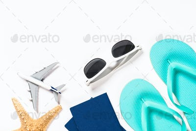Blue flip flops, sunglasses, passport, plane and starfish on white background