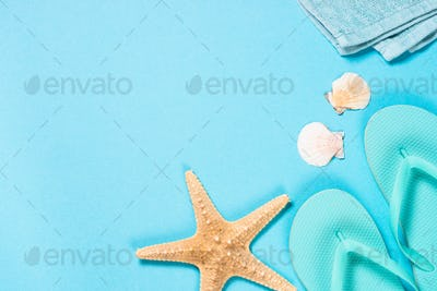 Blue flip flops, towel and starfish on blue background