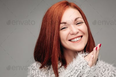 Charming woman with ginger hair smiling and putting hands together