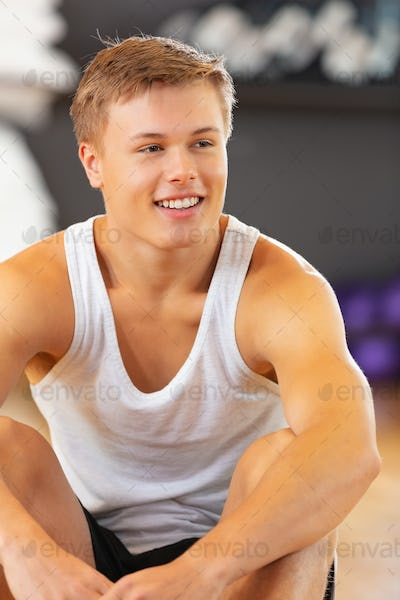 Smiling young man in workout outfit sitting on the floor at fitness gym