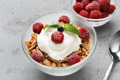 Granola, yougurt and raspberries in bowls