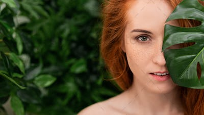 Portrait of young and beautiful woman in tropical leaves