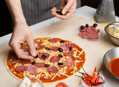 Pizza art. Chef adding olives to pizza