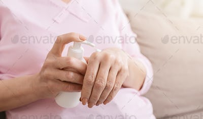 Hands senior woman with moisturizing cream closeup