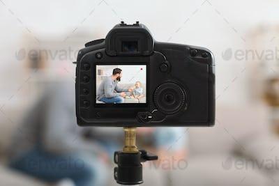 Millennial dad recording blog about feeding baby