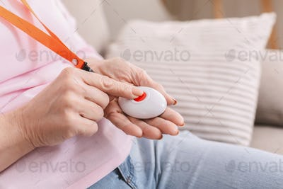Senior woman hand pressing Alarm Button, closeup