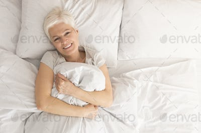 Attractive woman relaxing in bed, morning awakening, health and beauty, leisure