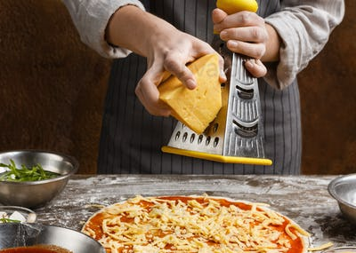 Woman sprinkling pizza with cheese, rubbing on grater