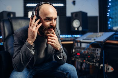 Sound producer in headphones listens composition