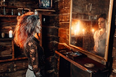 Witch at the mirror, young woman in the reflection