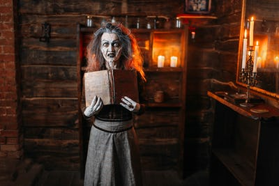 Witch holds spellbook, dark powers of witchcraft