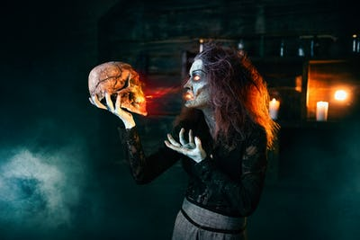 Scary witch holds human skull and reads the spell