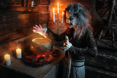 Scary witch reads spell over the pot, seance