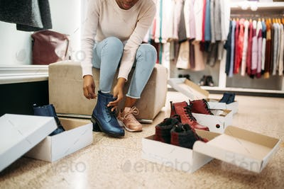 Black female person trying on shoes, shopping