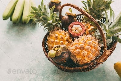 Ripe tropical fruits in a basket, pineapples, mangosteen